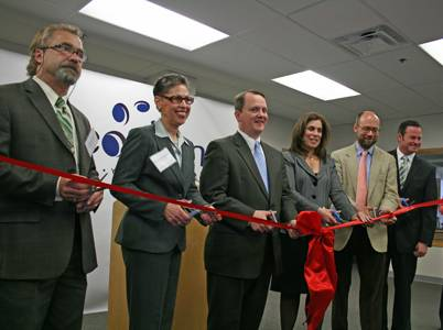 Photograph of Lieutenant Governor Timothy Murray and Susan Windham-Bannister cutting a ribbon at the opening of NeoStem in Cambridge.